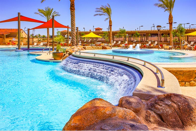Resort-style pool with cascading water and shaded areas in Sun City Festival in Arizona