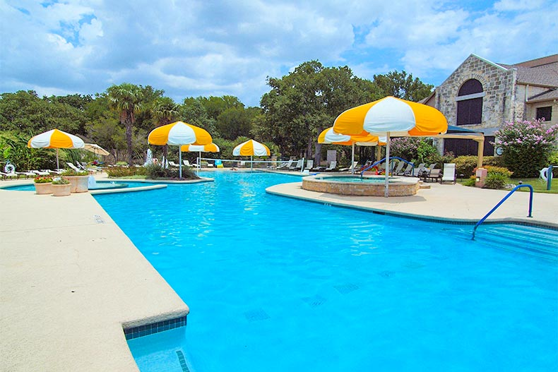 Pool with yellow and white umbrellas in Sun City Texas in Georgetown
