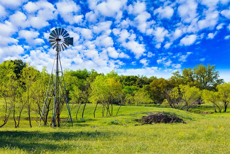 A windmill and picturesque greenery on a ranch in Texas Hill Country
