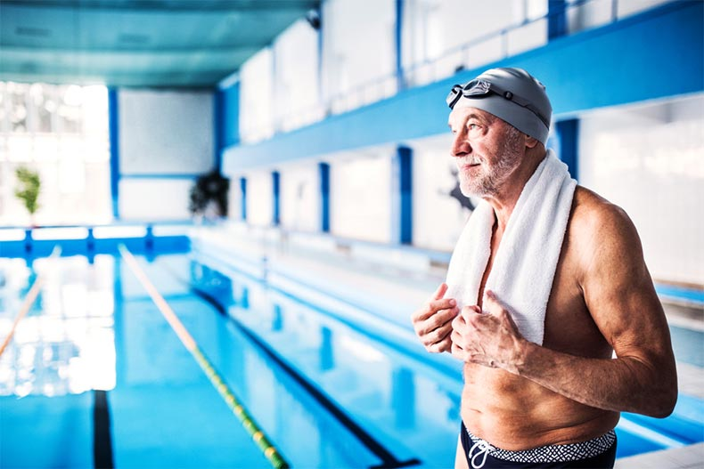 A senior man drying off after taking a swim at his community's indoor pool