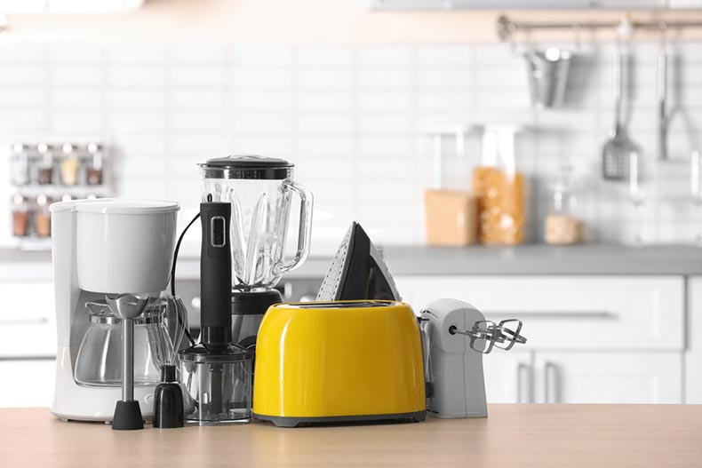 Household and kitchen appliances on table against a blurred kitchen background