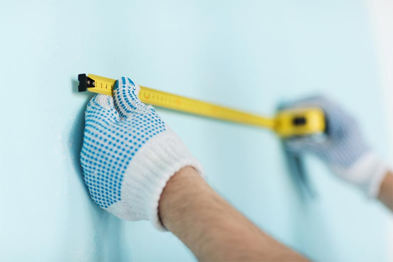 Closeup up on a man wearing gloves while using a tape measure on a wall
