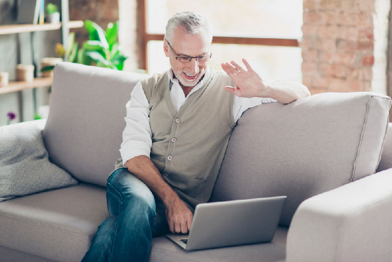 old man on couch smiling at computer screen wit video chat