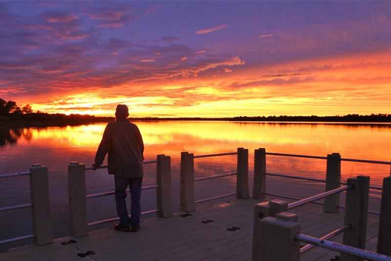 man standing on texas lake dock staring at colorful sunset