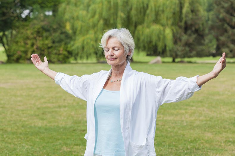 A senior woman practicing tai chi outdoors