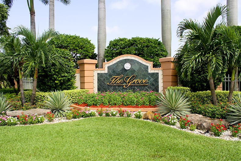 Well-manicured green landscaping surrounding the sign for The Grove in Boynton Beach, Florida