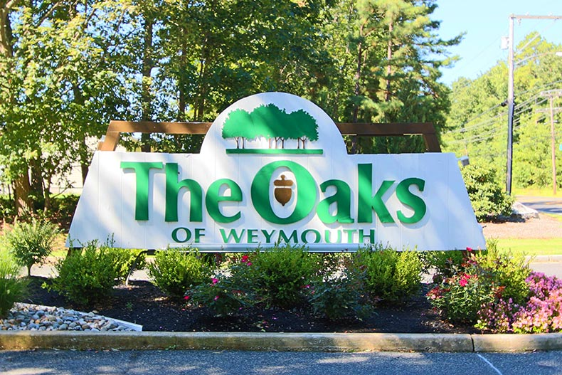 Greenery surrounding the community sign for The Oaks of Weymouth in Mays Landing, New Jersey