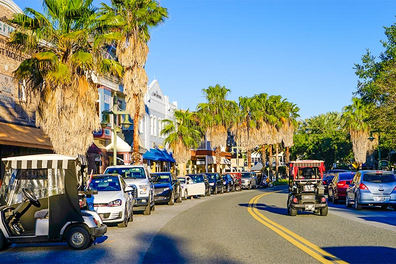 Golf carts parked and driving on a palm tree lined road in The Villages