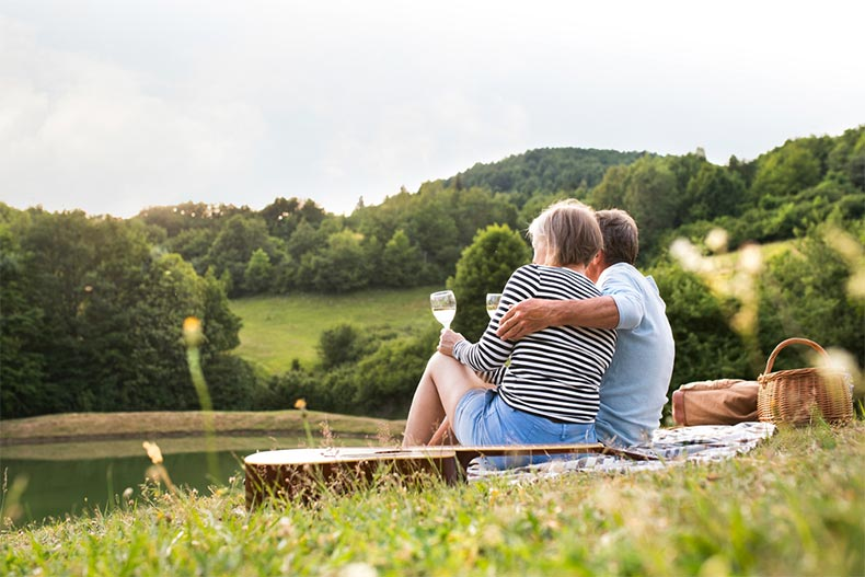 A senior couple relaxing with wine and a picnic on a hillside overlooking a lake
