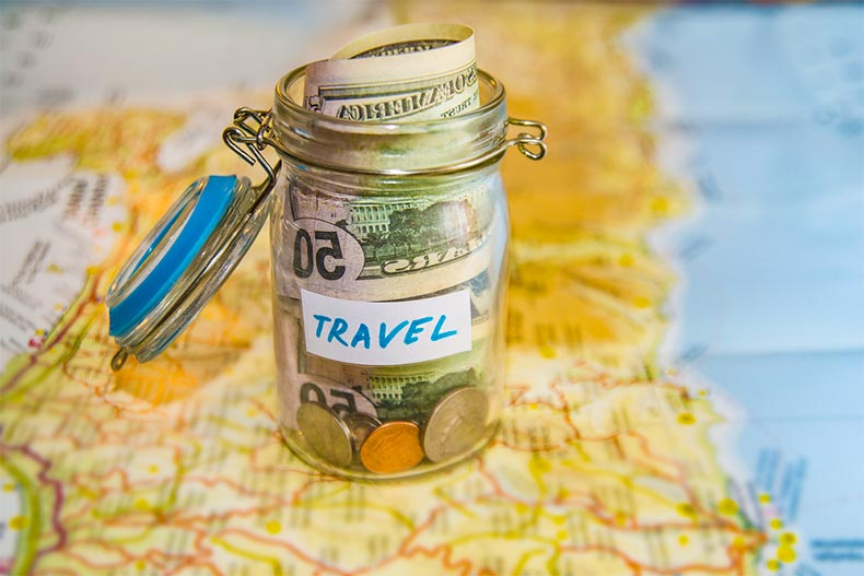 "A jar labeled ""travel"" and full of dollar bills and loose change"