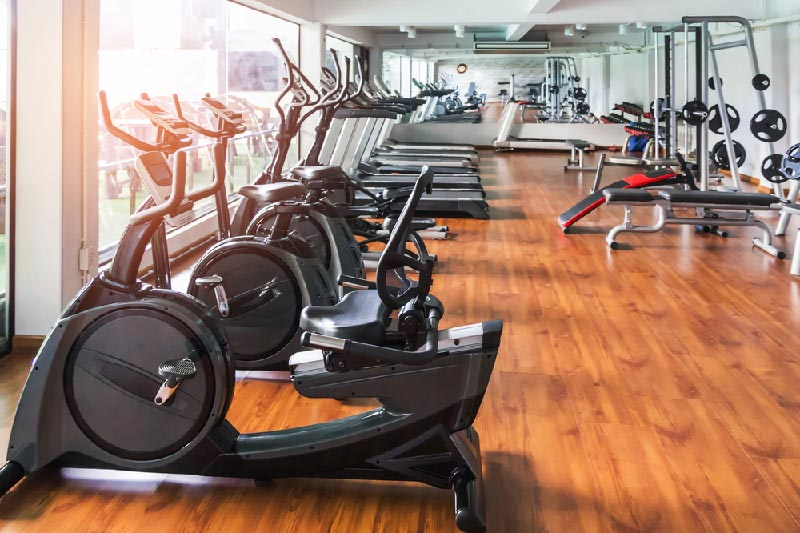 indoor fitness room with treadmills, bike machines, and weights.