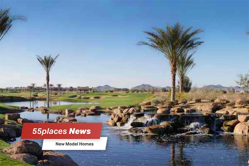 """New Model Homes"" banner over palm trees surrounding a pond at Trilogy at Encanterra in Queen Creek, Arizona"