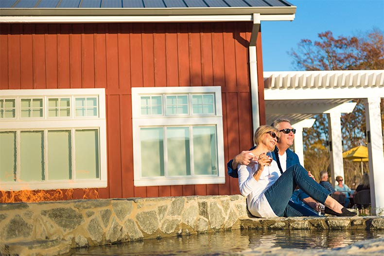 Older couple watching sunset next to a fountain and barn-style building in Trilogy Lake Norman