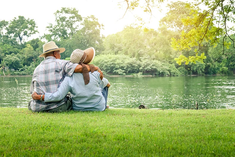 An older couple with their arms around each other sitting on the back of a picturesque river