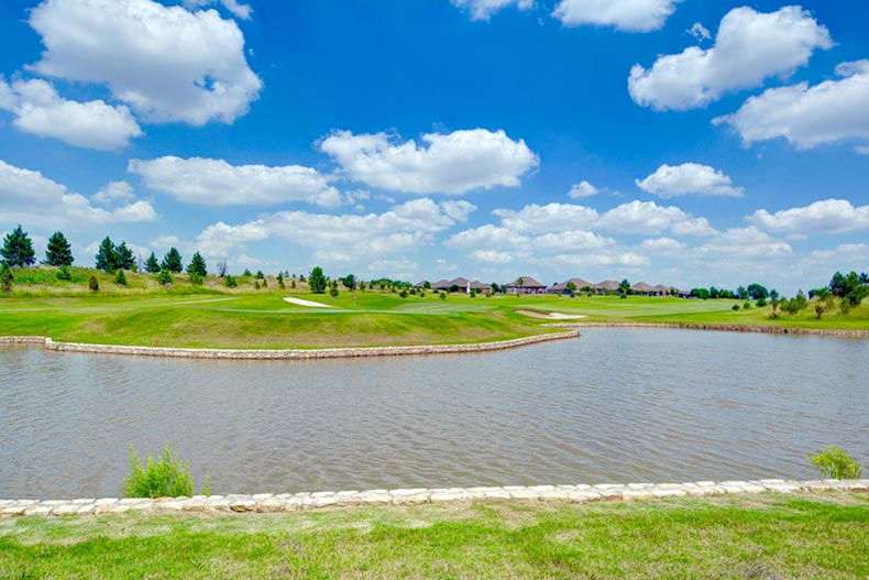 Blue sky over a pond and community greenspace at Frisco Lakes in Frisco, Texas