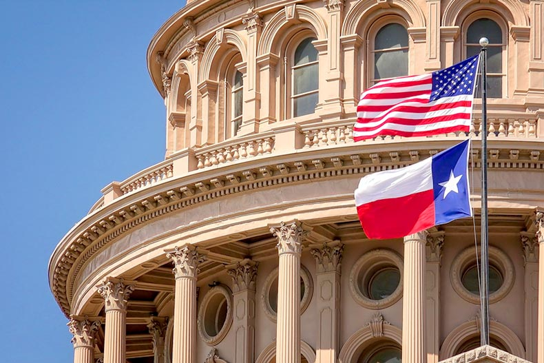 American and Texas flags flying on the dome of the Texas State Capitol building in Austin, Texas