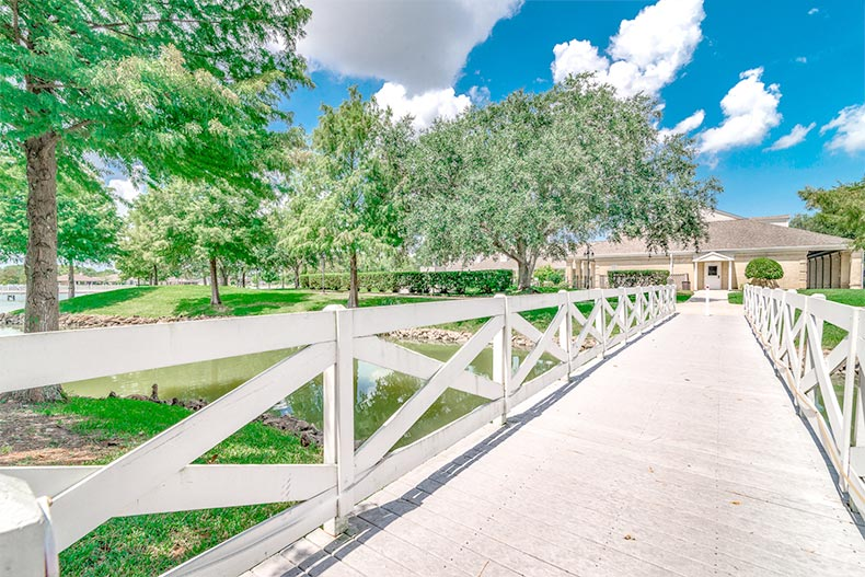 Green grass and trees surrounding a wooden walkway leading to the clubhouse at CountryPlace in Pearland, Texas