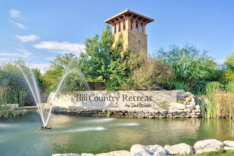 Blue sky over a fountain in front of the sign for Hill Country Retreat in San Antonio, Texas