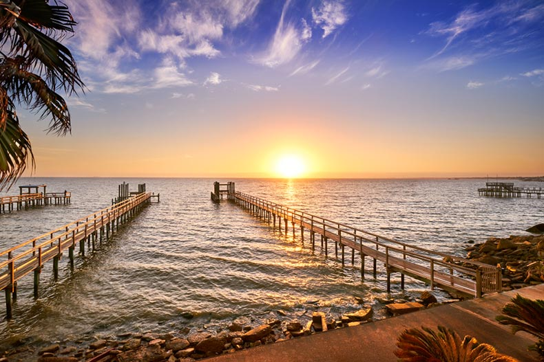 Sunset view of long wooden fishing docks stretching out into Galveston Bay, Texas
