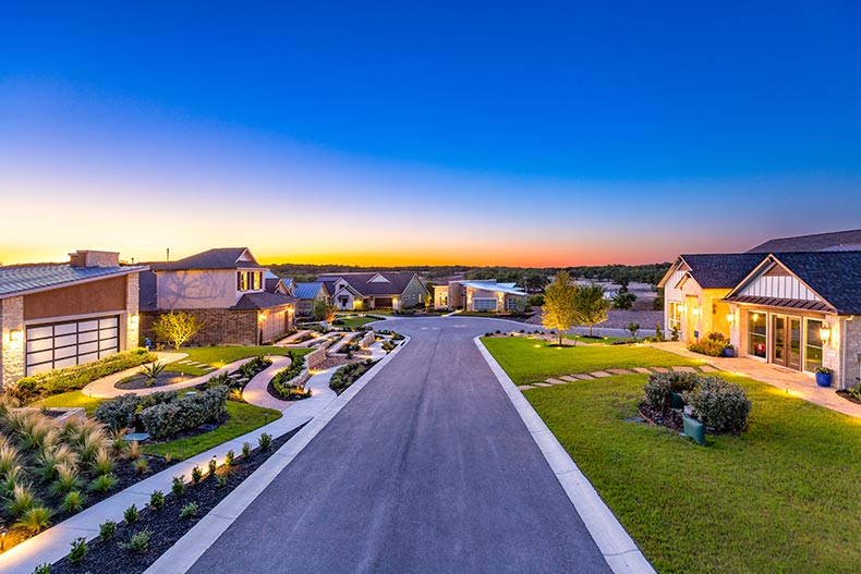 View of a street lined with model homes at Kissing Tree in San Marcos, Texas