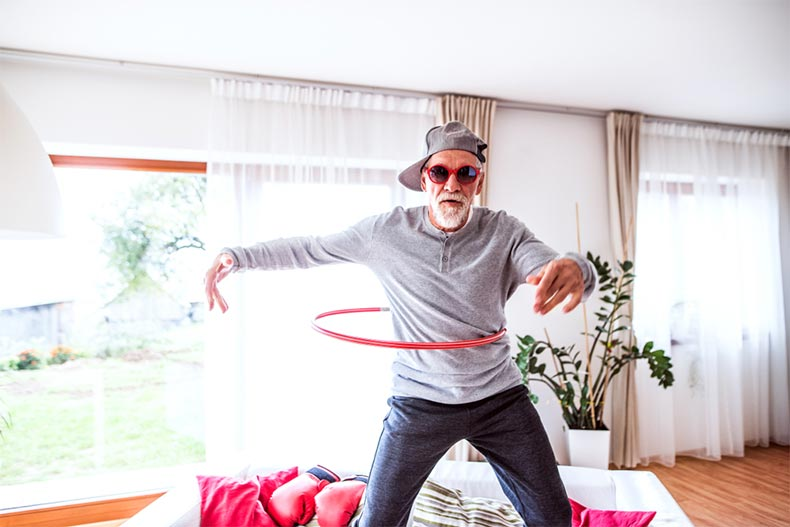 A senior man in silly sunglasses having fun with a hula hoop at home