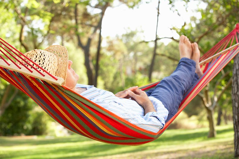 A senior man relaxing in a hammock on a sunny day