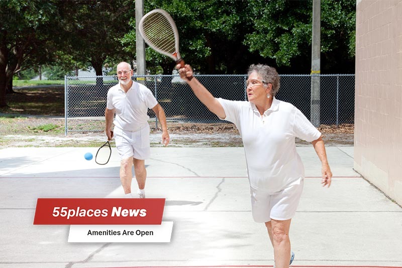 """55places News: Amenities Open"" banner over an active senior couple playing racquetball"