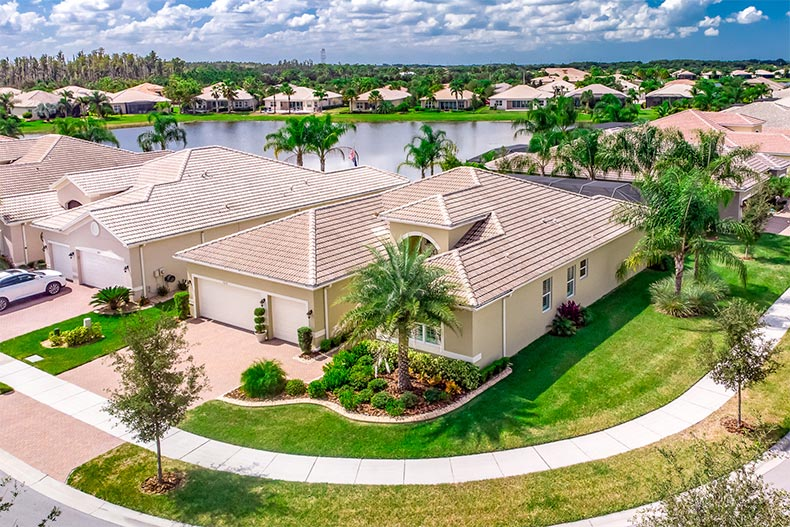 Aerial view of homes, palm trees, and a pond at Valencia Lakes in Wimauma, Florida