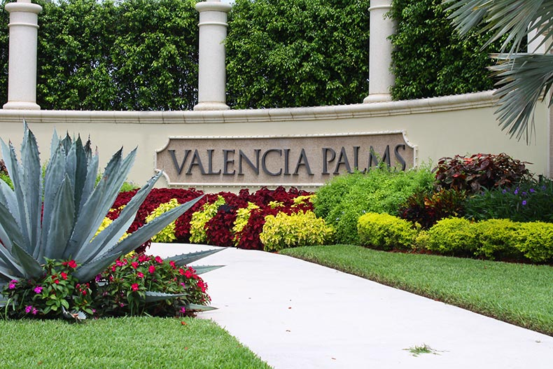Picturesque landscaping surrounding the community sign for Valencia Palms in Delray Beach, Florida