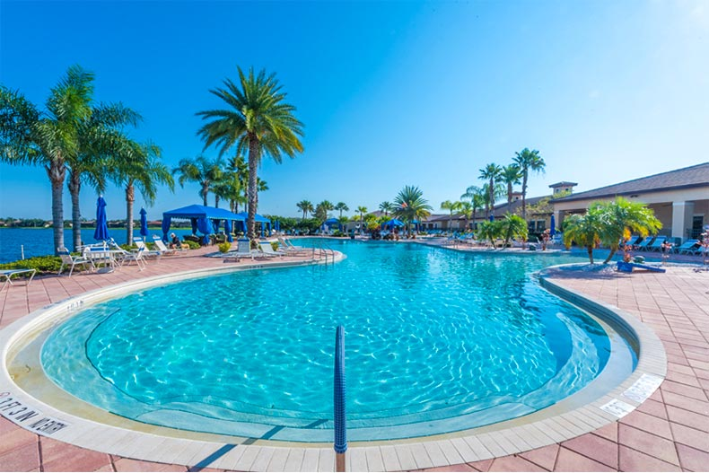 Valencia Lakes' zero-entry, resort-style pool with patio and palm trees surrounding.