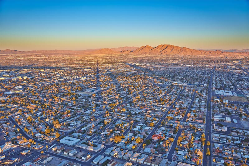 aerial view of homes and neighborhoods in las vegas with mountains in background.