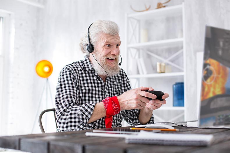 An older man with a headset on excitedly playing video games at his desk