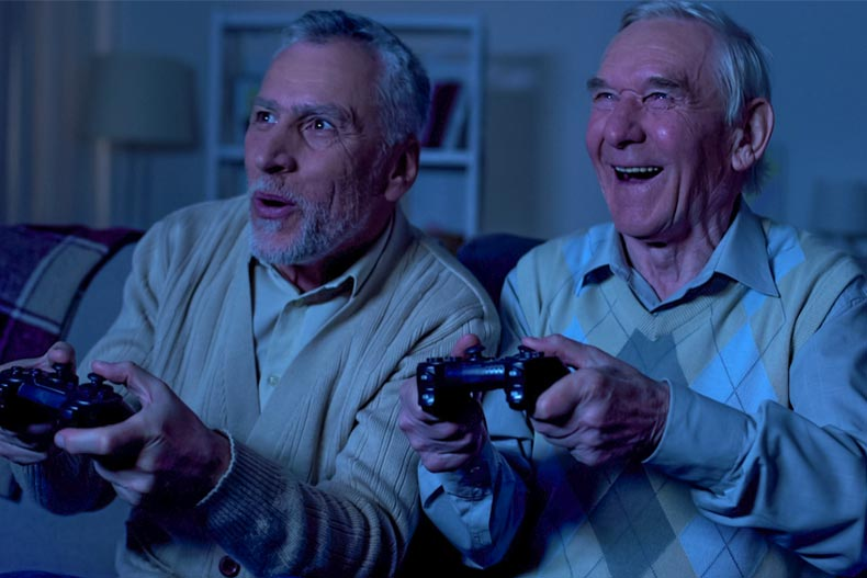 Two older men playing Playstation in a dark room