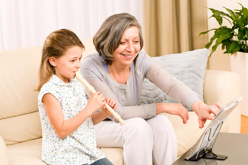 A senior woman smiling while sitting on a couch and teaching a young girl to play flute
