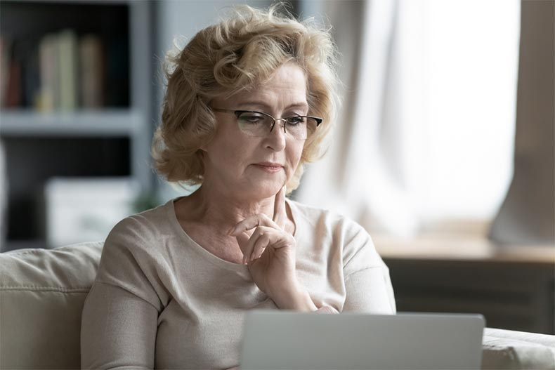 An older woman pausing to consider if what she's reading on her laptop is a scam