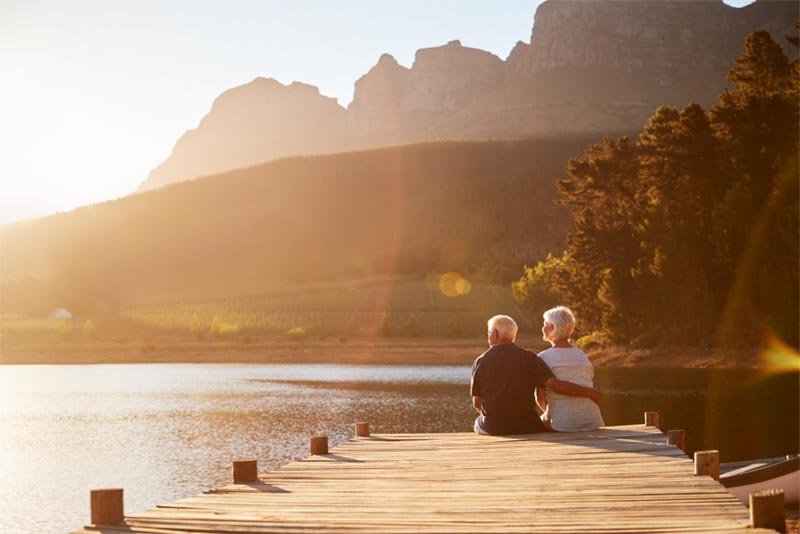 senior couple looking at sunset from dock on a mountain lake