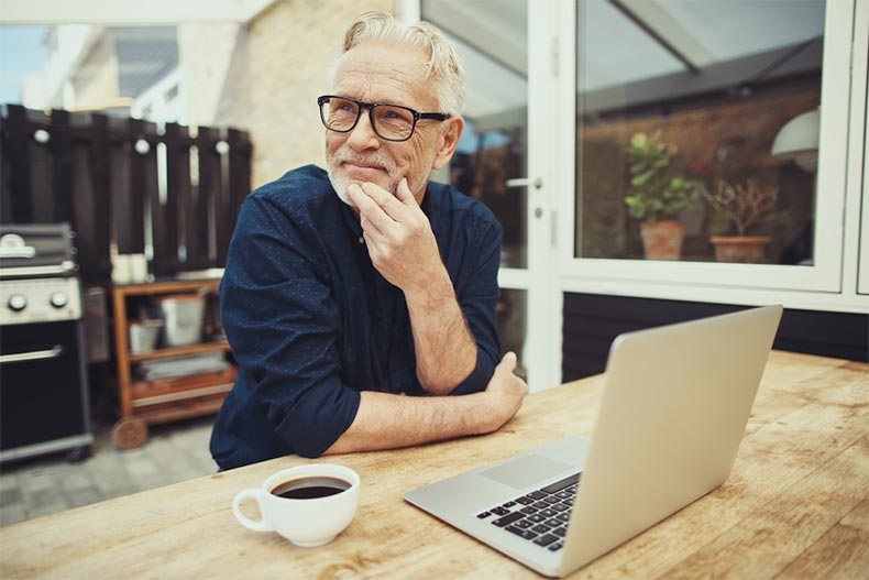 A senior man with a cup of coffee pausing to think while he works on his laptop