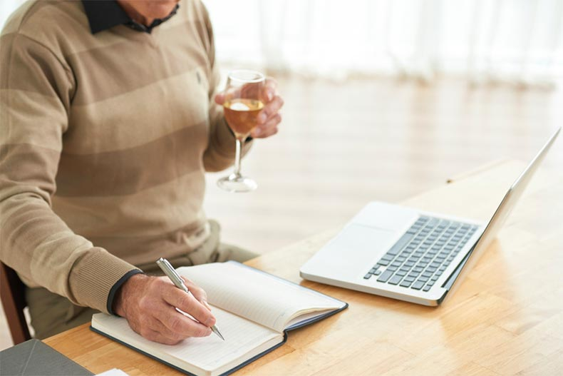 An older man sipping wine and taking notes during an online wine tasting