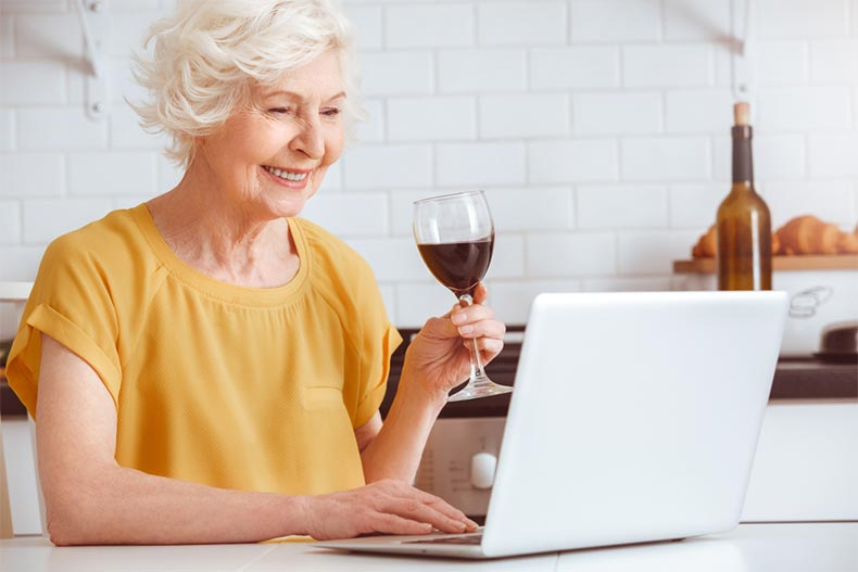 An older woman drinking wine while on a laptop in the kitchen