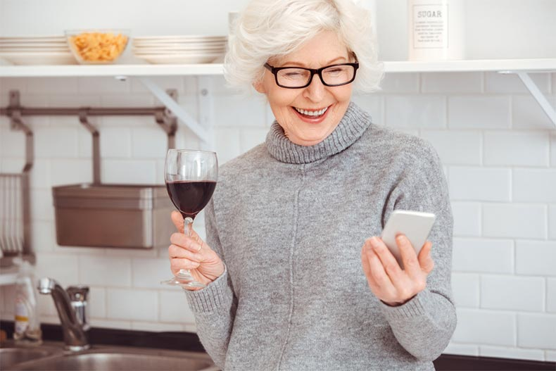 An old woman drinking wine while smiling and holding a smart phone