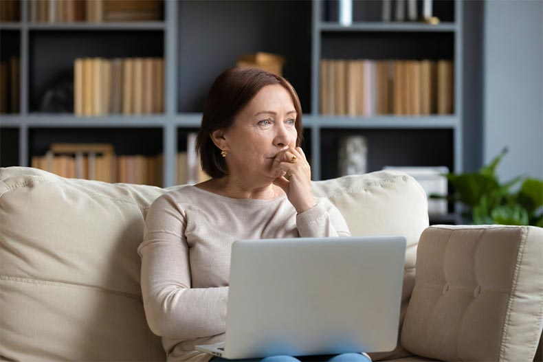 Woman sitting on the couch with laptop and thoughtfully looking into the distance.