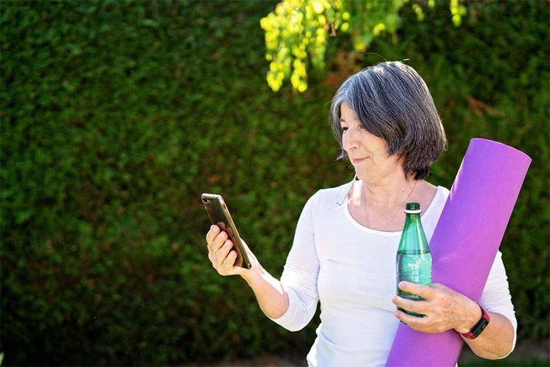 An older adult woman looking at her smartphone while holding a yoga mat and a water bottle