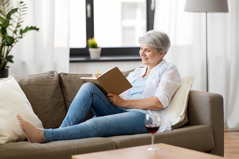 An older woman smiling while relaxing on a couch and writing in a journal