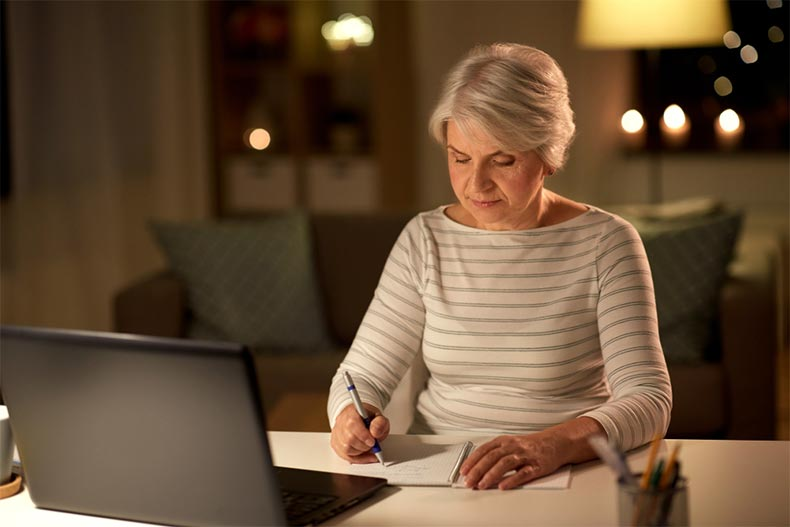 A senior woman writing in a notebook beside her laptop