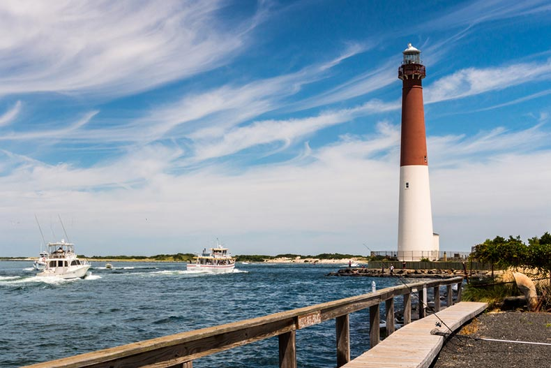 Fishing boats heading out to sea with the Barnegat Lighthouse in the background