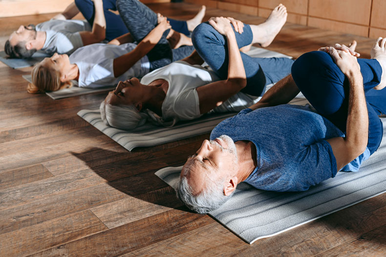 Group of active adults stretching during a yoga class.