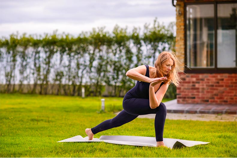 Older woman practicing yoga in a yard with gray skies