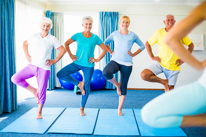 Older adults doing yoga guided by an obscured instructor