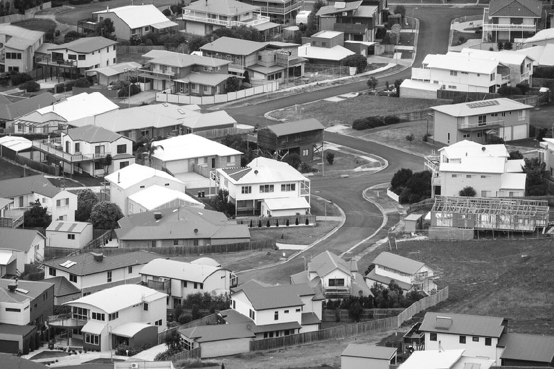 black and white aerial of community homes with road winding through