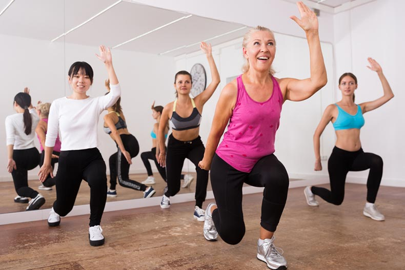 A group of women smiling while taking a zumba class in an aerobics studio